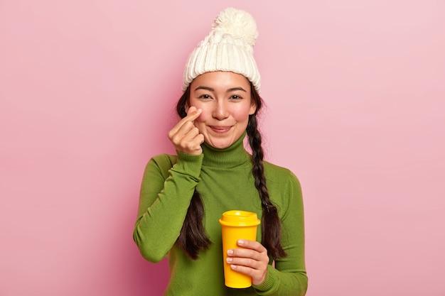 Jovem asiática atraente faz um sinal coreano, molda um coraçãozinho perto da bochecha, expressa amor ao namorado, usa um chapéu quente e um macacão casual, bebe café para viagem
