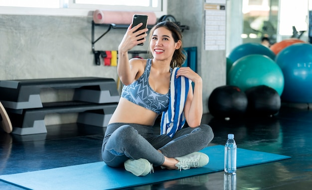 Jovem asiática atraente sorridente aptidão ativa sentado no chão do ginásio e tomando uma selfie.