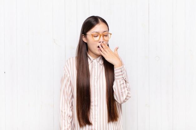 Jovem asiática bocejando preguiçosamente no início da manhã, acordando e parecendo sonolenta, cansada e entediada