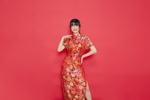 Jovem asiática bonita usando cheongsam com ação para o conceito de ano novo chinês