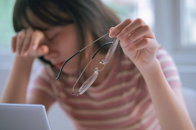 Jovem asiática cansada de trabalhar muito tempo no computador
