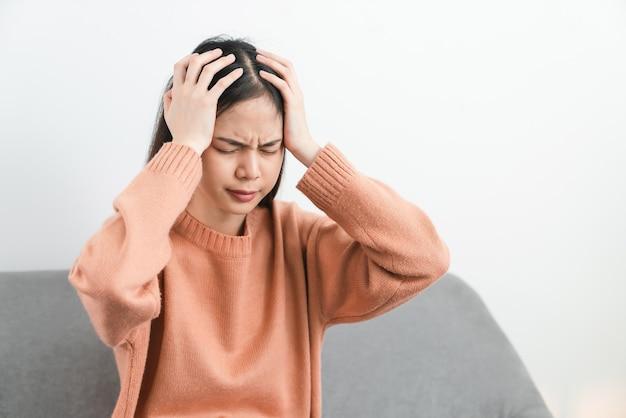 Jovem asiática cansada sentada e com dor de cabeça por causa da enxaqueca.