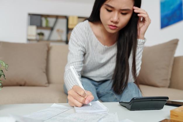 Jovem asiática carrancuda contando a soma das despesas mensais e contas de serviços públicos e fazendo anotações no caderno