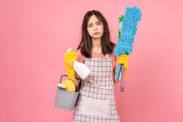 Jovem asiática chata usando avental com luvas de borracha amarelas e segurando um balde de material de limpeza no fundo rosa