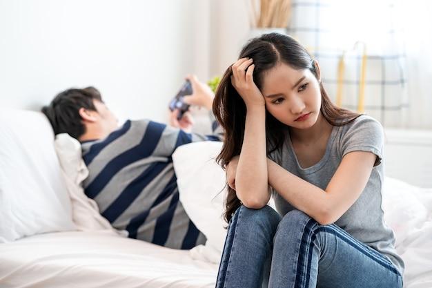 Jovem asiática chateada sentada na cama, contra o namorado, a esposa tem uma expressão de decepção e chateada com o marido.