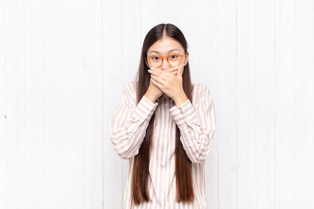 Jovem asiática cobrindo a boca com as mãos com um choque