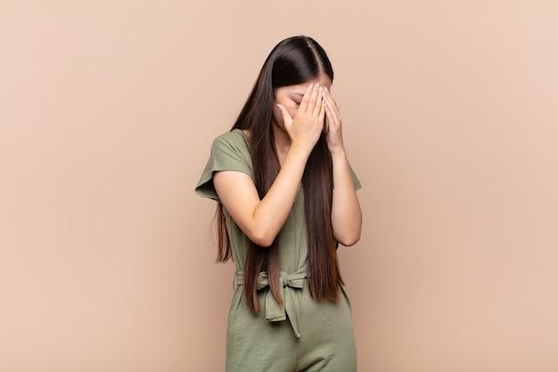 Jovem asiática cobrindo os olhos com as mãos com uma expressão triste e frustrada de desespero, chorando, vista lateral