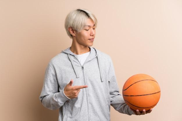 Jovem asiática com bola de basquete e apontando-o