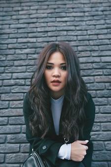 Jovem asiática com casaco escuro