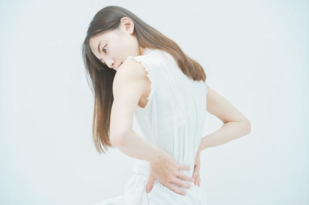 Jovem asiática com dor nas costas
