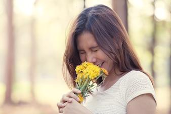 Jovem asiática com flor no parque em tom de cor vintage