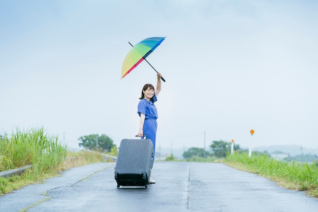 Jovem asiática com mala e guarda-chuva colorido