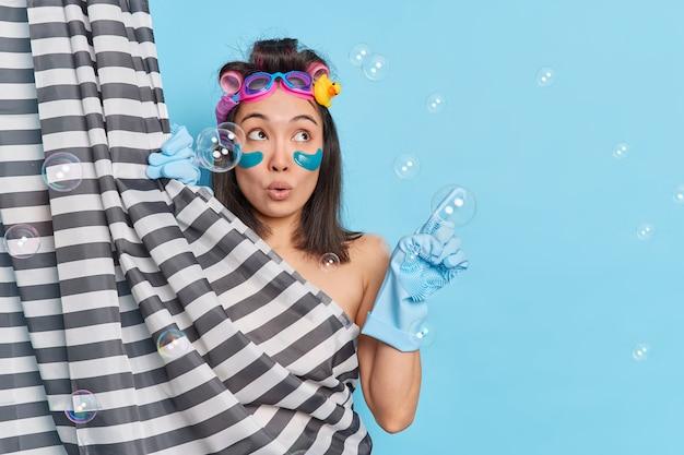 Jovem asiática com manchas na nuca, radiante e surpresa, segura a respiração de espanto, toma banho pela manhã indica ao lado mostra o espaço em branco isolado sobre o fundo azul torna o penteado encaracolado