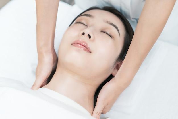 Jovem asiática com massagem na cabeça em um salão de estética