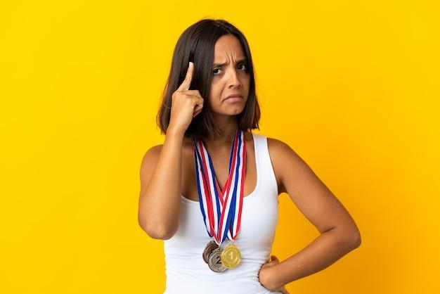 Jovem asiática com medalhas isoladas em branco pensando em uma ideia