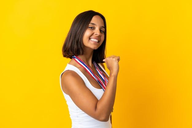 Jovem asiática com medalhas isoladas em um branco orgulhosa e satisfeita