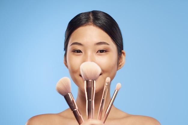 Jovem asiática com pincéis de maquiagem.