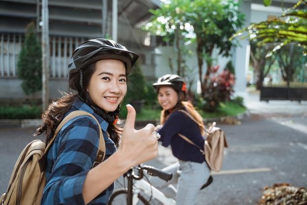 Jovem asiática com polegares para cima usando capacete e malas prontas para ir ao campus