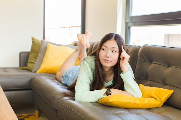 Jovem asiática com um olhar concentrado, pensando com uma expressão duvidosa