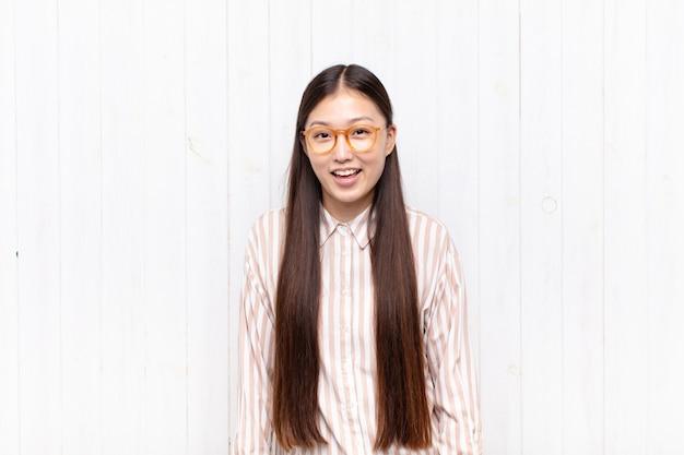 Jovem asiática com um sorriso grande, amigável e despreocupado, parecendo positiva, relaxada e feliz, arrepiante