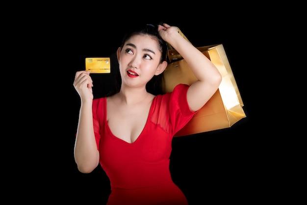 Jovem asiática com um vestido vermelho segurando um cartão de crédito e sacolas de compras