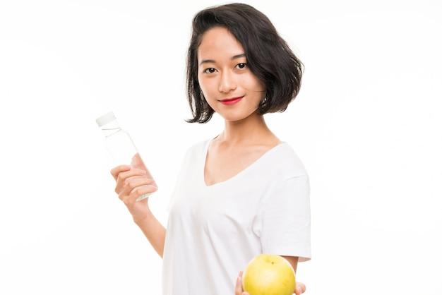 Jovem asiática com uma maçã e uma garrafa de água