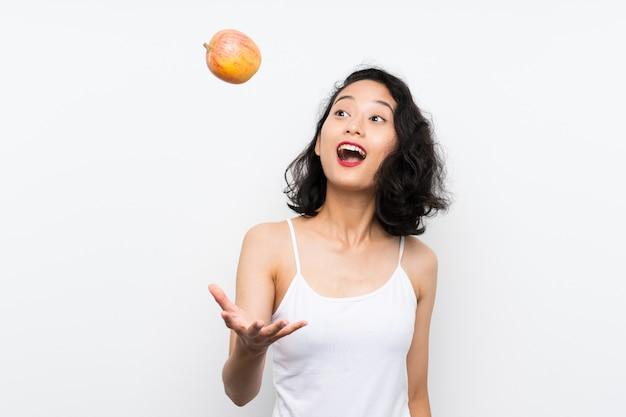 Jovem asiática com uma maçã sobre parede branca isolada