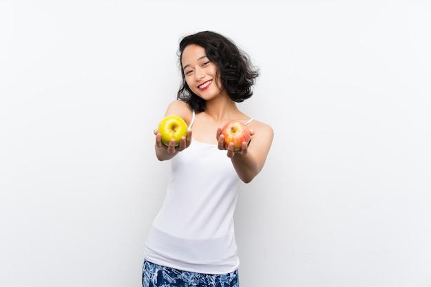 Jovem asiática com uma maçã sobre parede branca