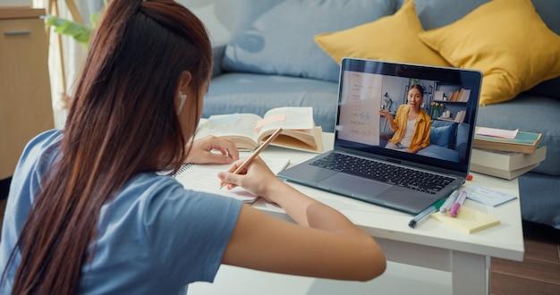 Jovem asiática com videochamada para computador portátil de uso casual, aprender on-line com o professor, escrever palestra, caderno, sala de estar em casa