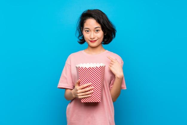 Jovem asiática comendo pipocas com expressão facial de surpresa