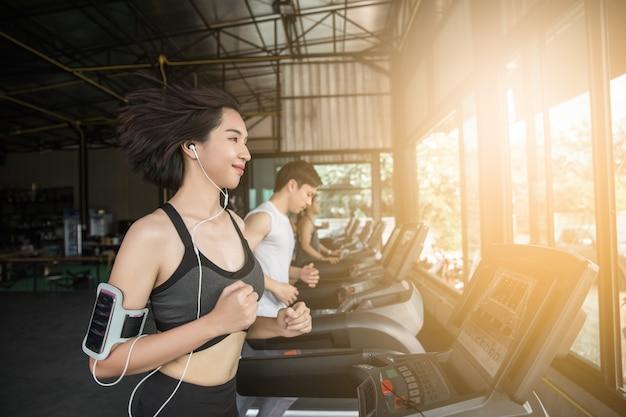 Jovem asiática correndo muscular na esteira