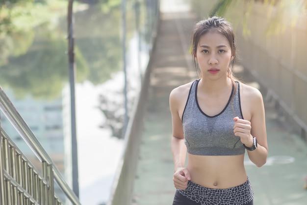 Jovem asiática correndo na calçada pela manhã