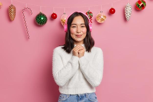 Jovem asiática de aparência agradável mantém as mãos unidas, tem bom humor e usa um suéter branco confortável ouve uma melodia agradável em poses de fones de ouvido
