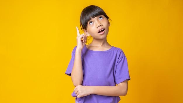 Jovem asiática de camisa violeta pensando e apontando para cima para a ideia,