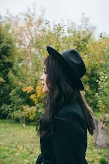 Jovem asiática de casaco escuro e chapéu