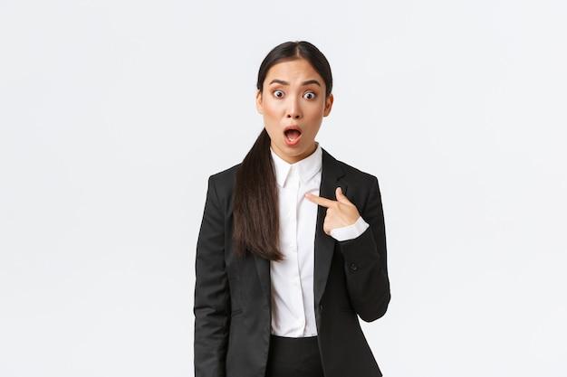 Jovem asiática de terno chocada e ofendida, apontando para si mesma com uma expressão de pânico perplexa, sendo acusada. mulher de negócios parecendo insultada ao ser nomeada, fundo branco
