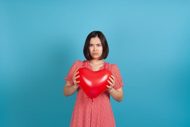 Jovem asiática decepcionada segurando um balão vermelho em forma de coração no dia dos namorados