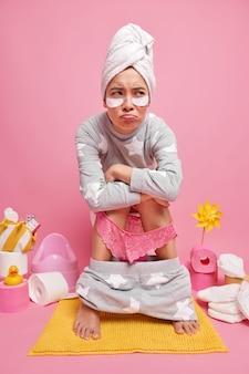 Jovem asiática descontente com constipação ou hemorróidas poses no vaso sanitário aplica manchas de beleza sob os olhos, vestida com um pijama macio, tem dor de estômago isolada sobre a parede rosa