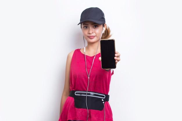Jovem asiática desportiva demonstrando telefone celular em fundo branco