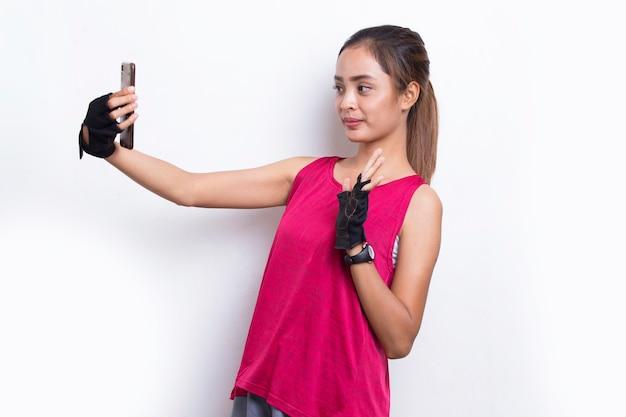 Jovem asiática desportiva usando telefone celular em fundo branco