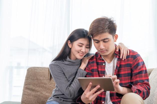 Jovem asiática e homem bonito, sentado no sofá usando o dispositivo
