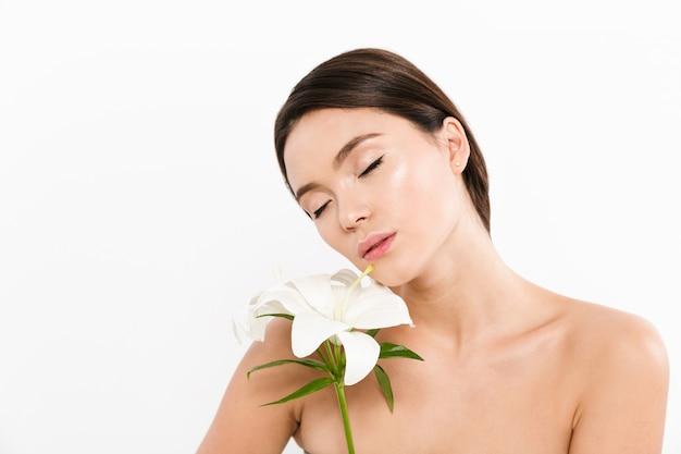 Jovem asiática em pé isolado com os olhos fechados e segurando a flor no ombro
