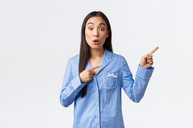Jovem asiática empolgada e interessada em um pijama azul, olhando curiosa para a câmera e fazendo perguntas