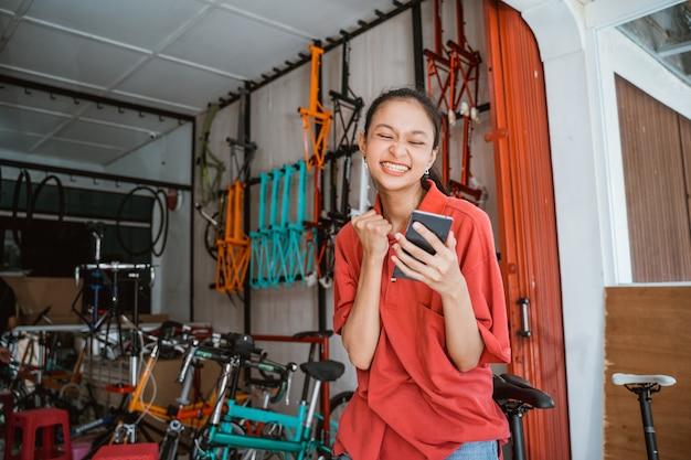 Jovem asiática empolgada em uma loja de bicicletas surpresa enquanto olha para o telefone