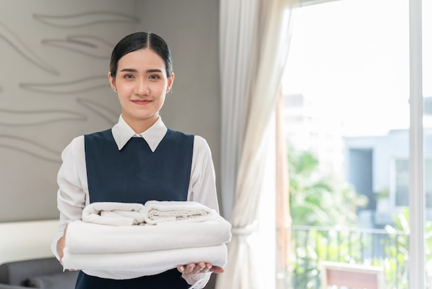 Jovem asiática empregada doméstica de uniforme segurando toalhas brancas e limpas no quarto do hotel