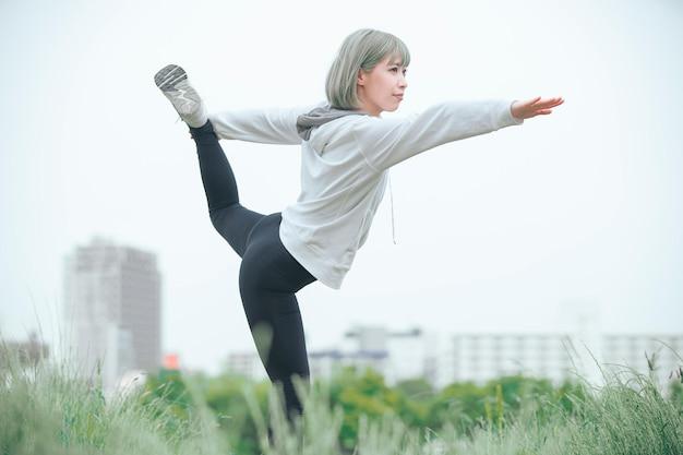 Jovem asiática exercitando ao ar livre