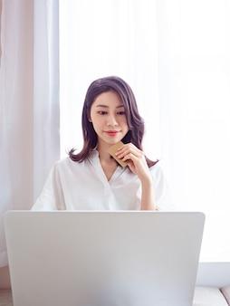 Jovem asiática fazendo compras online com cartão de crédito e laptop