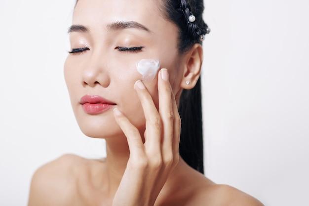 Jovem asiática fechando os olhos e aplicando um creme hidratante anti-envelhecimento no rosto