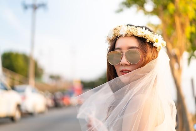 Jovem asiática feliz com véu de noiva