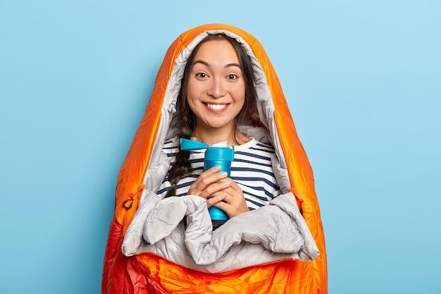 Jovem asiática feliz se aquece em um saco de dormir, segura um frasco azul com uma bebida aromática quente, sente-se relaxada, passa o tempo livre na natureza, isolada sobre uma parede azul
